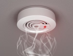 A fire alarm and smoke detector on a wall
