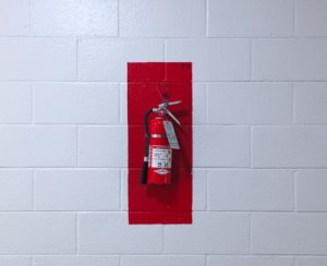 A fire extinguisher on a white wall.